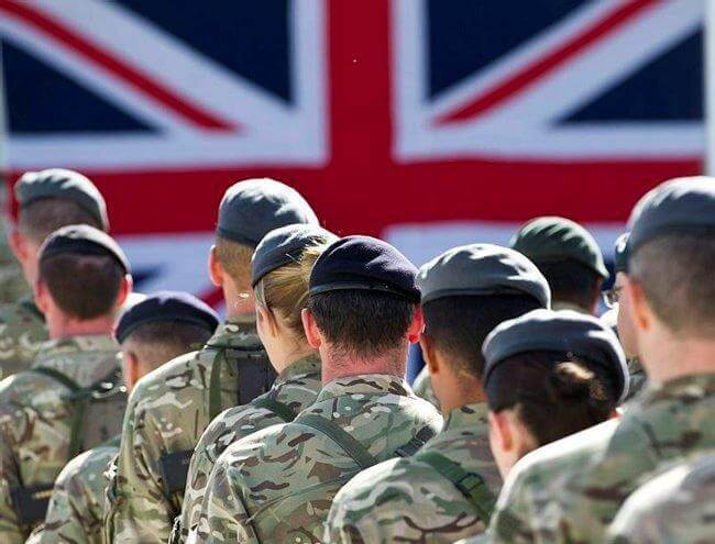 a line of soldiers facing the UK flag