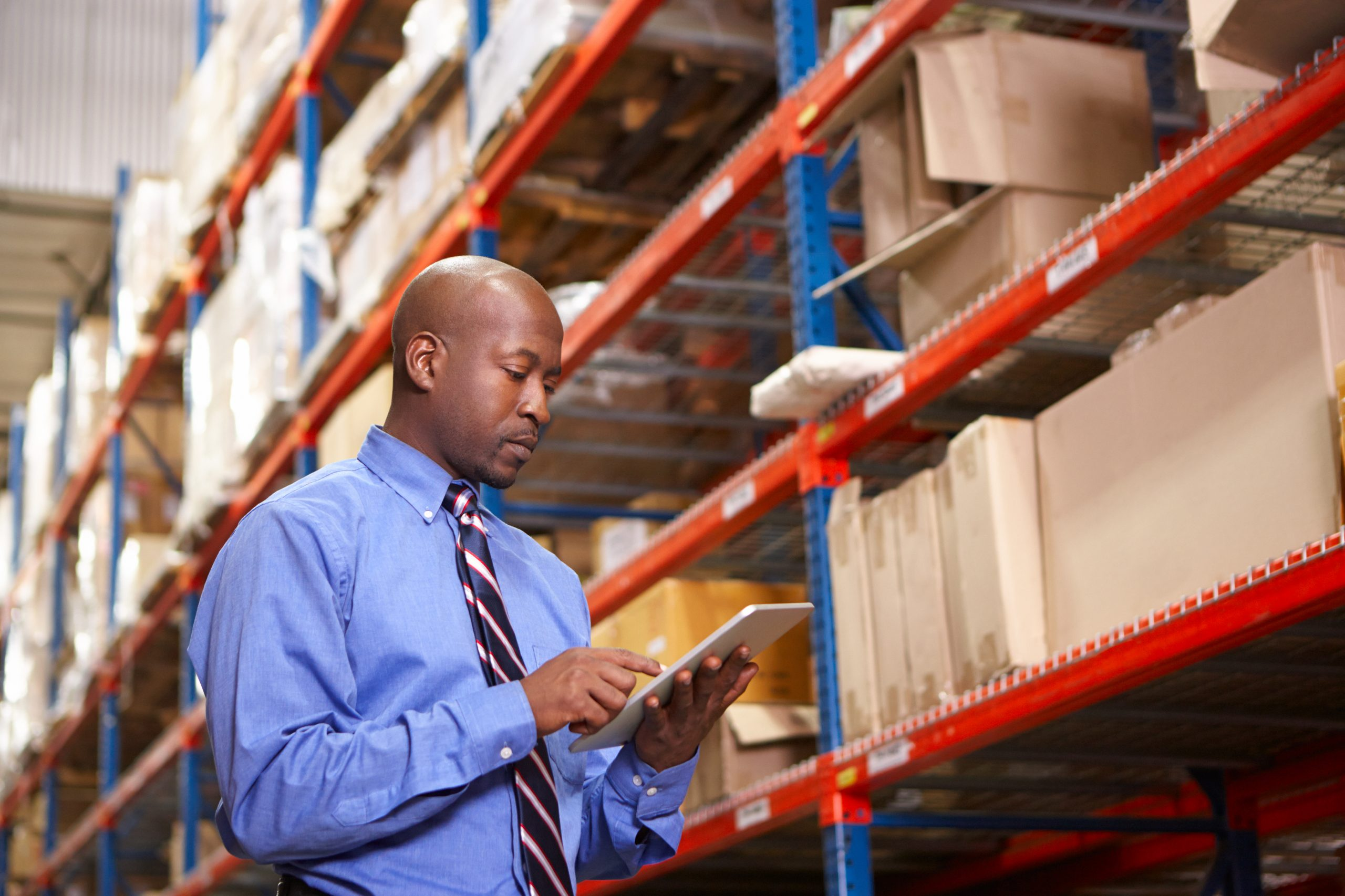 Warehouse manager looking at tablet and reviewing storage procedures